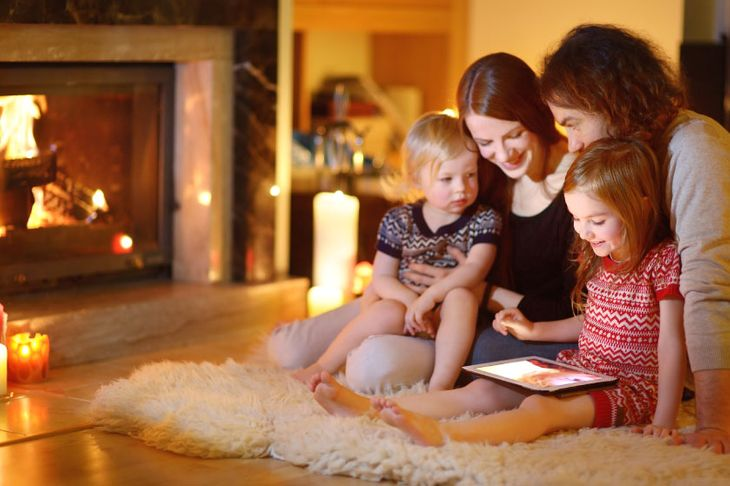 Young family in front of gas fireplace at home
